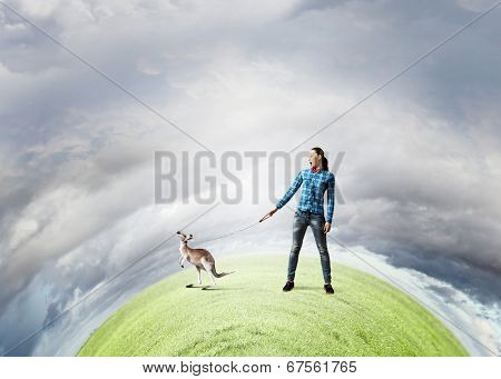 Young woman in casual holding kangaroo on lead poster