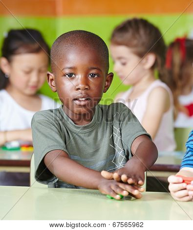 African child playing with dough at the table in a kindergarten