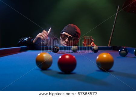 Man in sunglasses and a cap playing pool in a shadowy nightclub standing surveying the lay of the balls on the table smoking e-cigarette or e-shisha