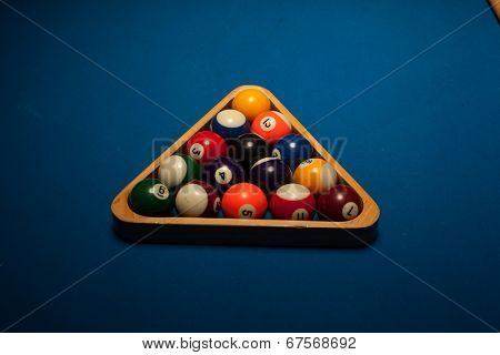Colorful numbered pool object balls in a wooden triangular rack ready to start a new game or frame on blue baize