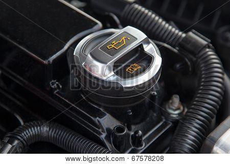 Motor oil cap under the hood of a car