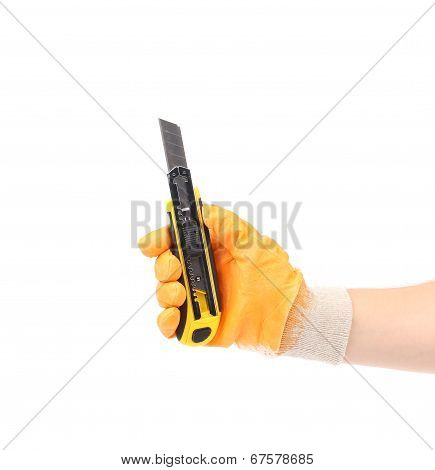 Hand holds yellow stationery knife.