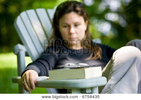Woman Contemplating After Reading Outside