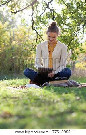 woman sitting on bedding on green grass with tablet during picnic in the park