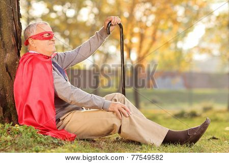 Senile old man sitting outdoor in a superhero costume