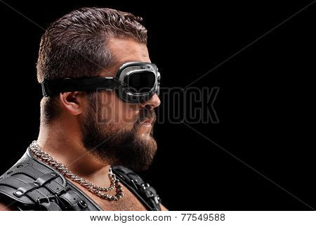 Male biker with goggles on black background
