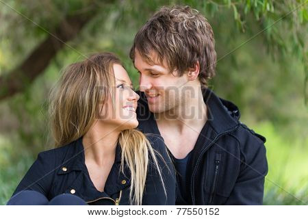 Happy young attractive smiling couple looking at each other enjoy their time outdoor