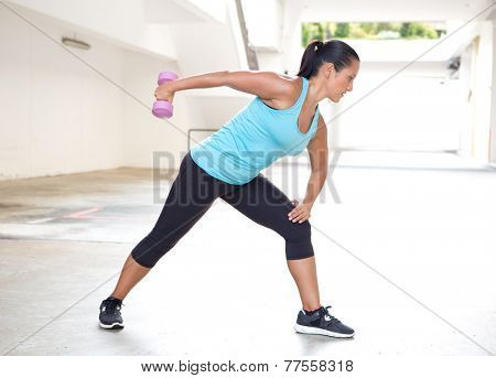 Beautiful sport woman in blue with dumbbell doing tricep back extension exercise