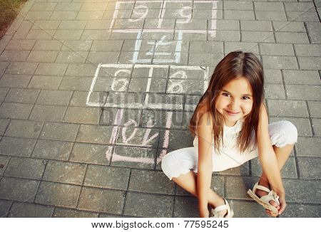 Beautiful Cheerful Little Girl Playing Hopscotch On Playground