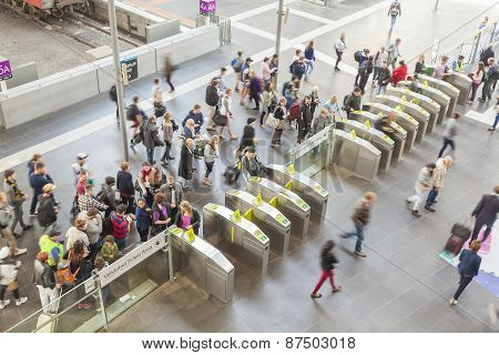 People passing through the gates at a railway station