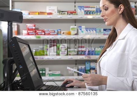 Pharmacist with prescription at the computer
