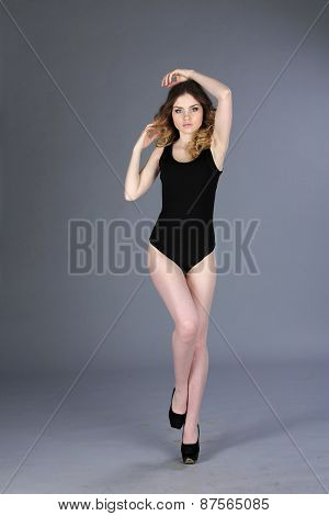 Young slim glamour woman dressed in black sport combidress
