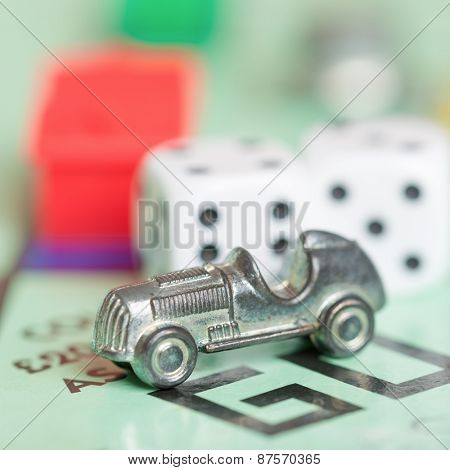 LONDON,UK - APRIL 1,2015 : Car token and dice on a vintage monopoly game board