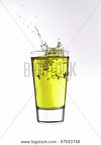 Splash in a glass of yellow lemonade isolated on white background