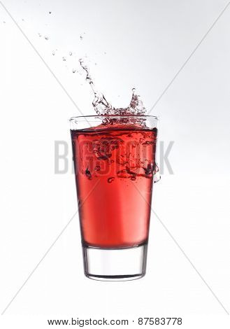 Splash in a glass of red lemonade isolated on white background