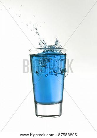Splash in a glass of blue lemonade isolated on white background