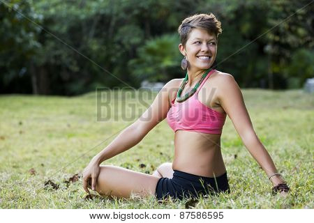 Woman practicing yoga outdoors - twists are detoxifying