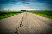 An old cracked damaged and repaired country asphalt road stretches ahead toward its vanishing point on the distant horizon with corn fields on either side. poster
