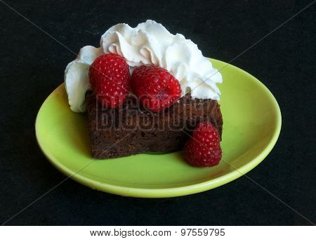 A tempting chocolate brownie is crowned with luscious whipped cream and three plump raspberries.