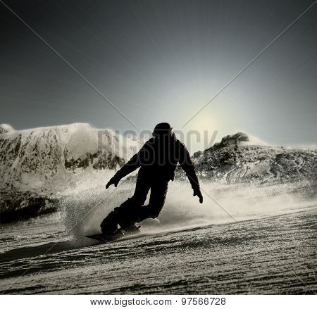 A silhouette of a snowboarder going down the hill in the opposing sunlight
