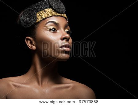 African girl with bright makeup and creative gold accessories on the head. Beauty face.