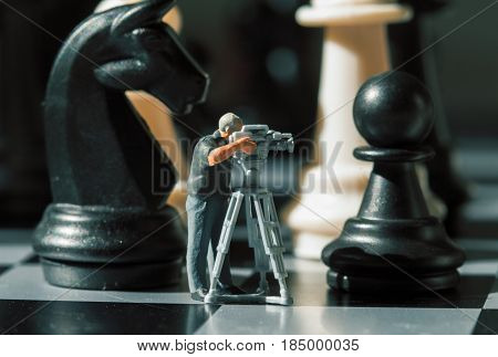 Cameraman miniature doll and chess figures on board. Filming the checkmate game. Black knight and pawn in camera. News making about chess. Videographer macro photo. Making movie with chess figures