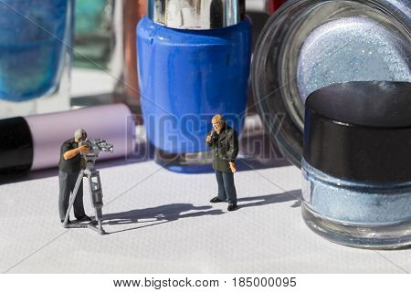 Television journalist miniature dolls. Reportage of women's cosmetic. Beauty industry news online broadcasting. People professions scene with reporters. Nail polish bottle and eye shadow macro photo