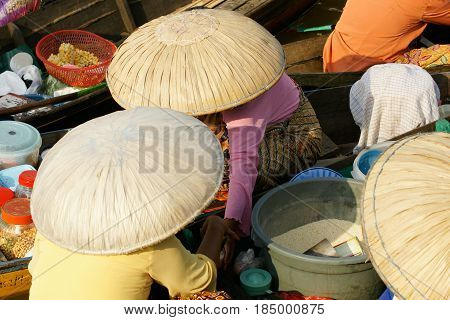Asian women wearing big round beige colored hats sitting in and selling from their small wooden boats on a floating market to make a living.