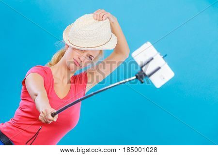 Technology modern photography confidence conept. Happy attractive adult blonde woman with sun hat taking funny picture of herself with smartphone on selfie stick.