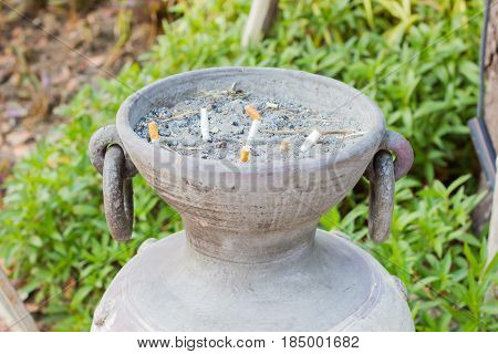 closeup smoked Cigarettes Butts in a public ashtray jar