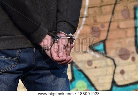 Rear view of the arrested and handcuffed offender against the graffiti background. The concept of preventing property damage vandalism and combating hooliganism. anti-bullying concept poster