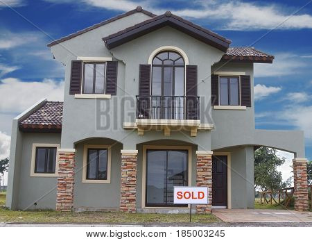 Real estate sign in front of a house for sale with blue clouds.