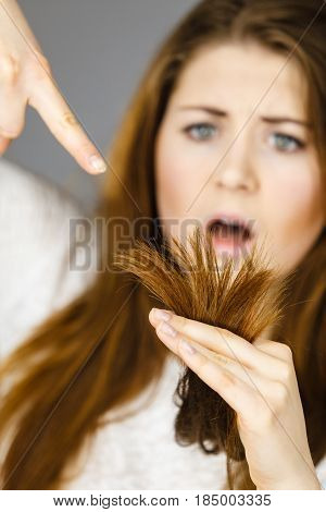 Worried woman looking at her dry split long brown hair ends thinking of good treatment. Haircare and hairstyling concept.