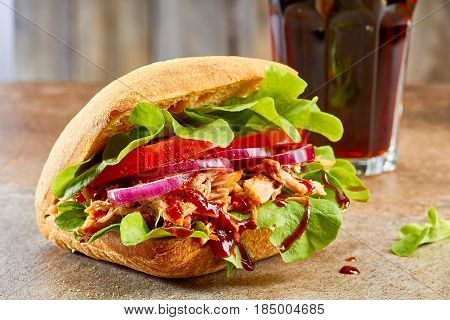 Sandwich with pulled pork, salad, tomato and glass of cola on stone table