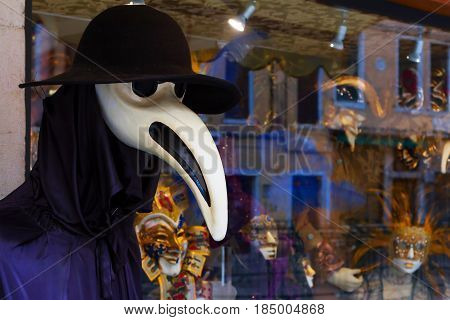 VENICE-JANUARY 12 2017. Different carnival masks in a showwindow of souvenir store and a manikin dressed in a plague doctor costume behind it. January 11 2017 Venice Italy.