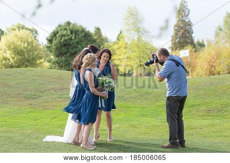 EUGENE, OR - SEPTEMBER 3, 2016: Wedding photographer with camera photographing bridesmaids and the bride at a golf course wedding at Shadow Hills Country Club.