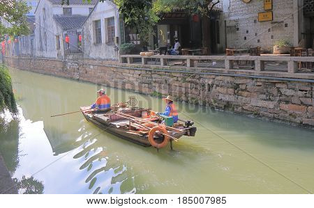 SUZHOU CHINA - NOVEMBER 3, 2016: Unidentified people clean canal in Pingjiang historical district. Pingjiang historical street was a major thoroughfare of eastern Suzhou in Southern Song Dynasty.