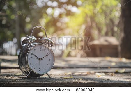 Clock on wood in the morning blurred nature background.