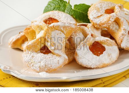 plate of tea cakes with apricot jam filling on yellow dishtowel - close up