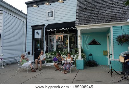 HARBOR SPRINGS, MICHIGAN / UNITED STATES - AUGUST 4, 2016: A small audience sits in front of the Monogram Goods store on Main Street, and listens to live music performed during the Street Musique event in downtown Harbor Springs.