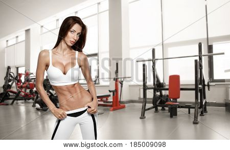 Young beautiful athlete woman in the gym. Fitness body, healtly lifestyle, sportly girl.