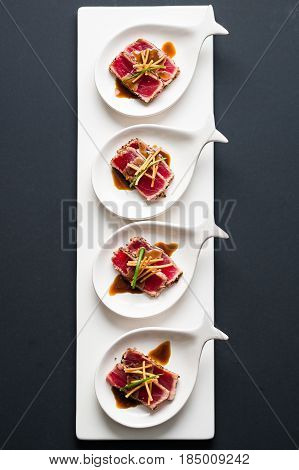 Tuna Tataki Sushi Top Centered View. Tuna Tataki is a Japanese dish which consist of briefly seared tuna steak in thin slices. Served as appetizer with brandy sauce and garnish on a dark background.