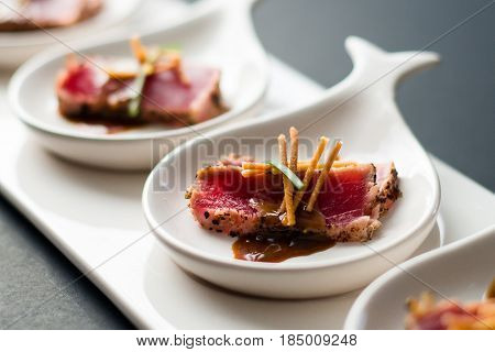 Tuna Tataki Close Up. Tuna Tataki is a Japanese dish which consist of briefly seared tuna steak in thin slices. Served as appetizer with brandy sauce and garnish on a dark background.