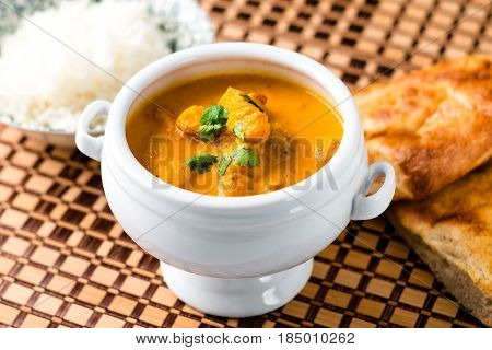 Delicious butter chicken served in a white bowl with naan bread and rice on the side on a wooden place mat.