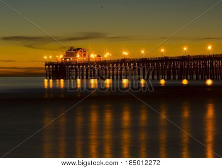 Sunset at Oceanside California pier showing the resturant at the end of the pier.