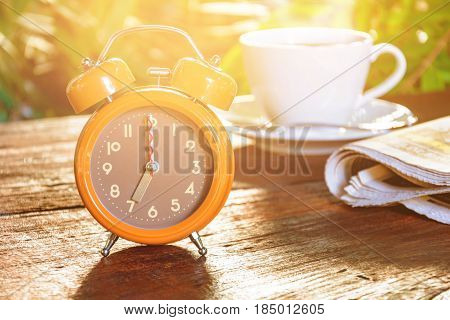 Coffee Cup Clock And News Paper On Old Wooden Table