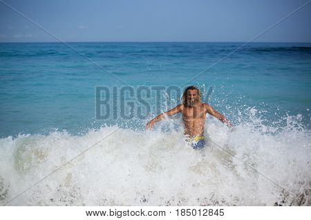 Handsome bearded curly man with naked torso and closed eyes is standing on the shore of the ocean and is opposing to the wave by his back and open arms and smiling