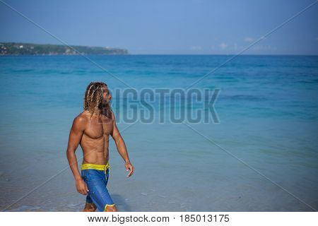 Half-length portrait of an handsome muscular bearded curly blond man in a blue shorts and with naked fit torso is walking along the water of the ocean and looking away