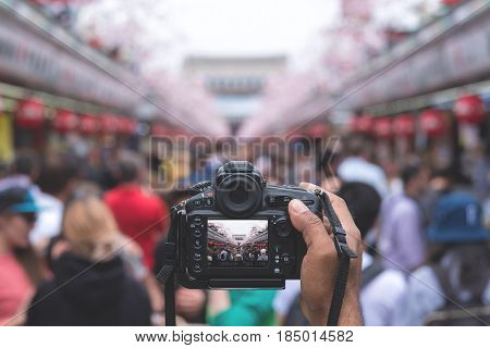 Camera capturing Senso-ji temple walking street (Nakamise) with many tourists in background.