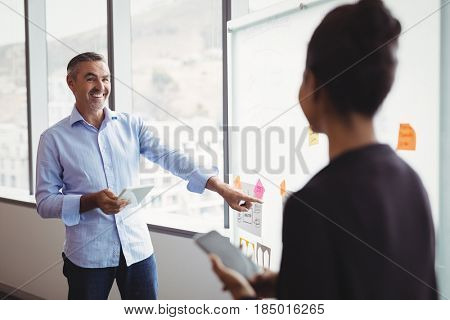 Colleagues discussing over sticky note in office